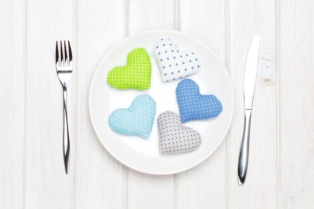 접시와 식기에 발렌타인 데이 장난감 마음입니다. 흰색 나무 테이블 위에 위에서 보기