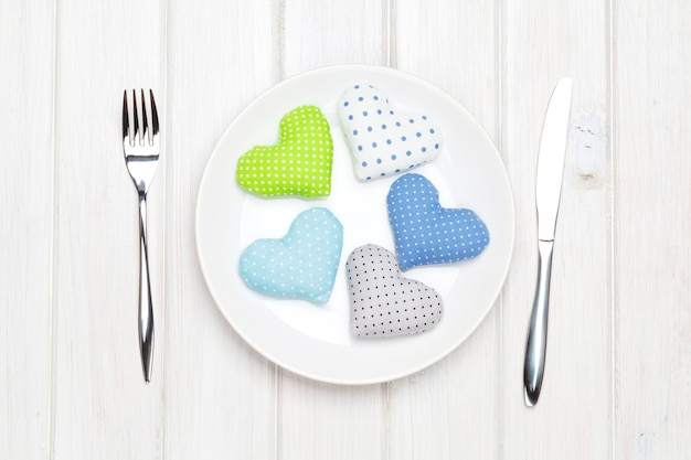 Valentines day toy hearts on plate and silverware. view from above over white wooden table