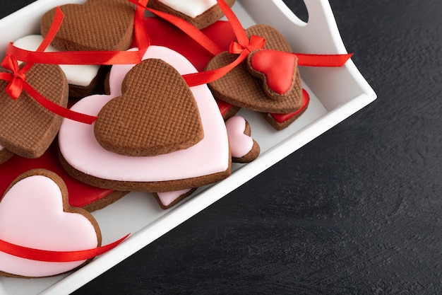 Valentines day treat. delicious homemade heart shaped cookies on black background close up.