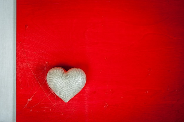 Valentines day. wedding day.  silver heart on red wooden background.