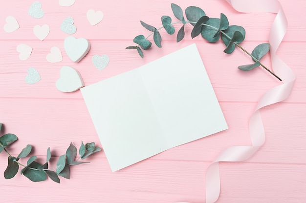 Valentines day or wedding flat lay with blank card, eucalyptus leaves frame paper hearts confetti