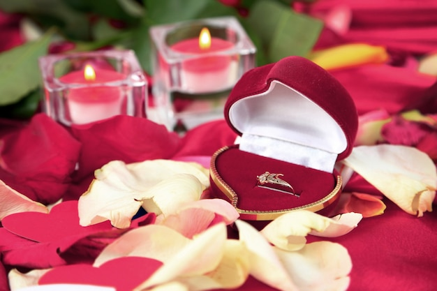Valentines day. wedding ring on rose petals background