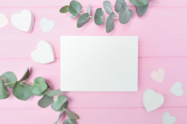 Valentines day or wedding valentine dating scene with blank sheet, eucalyptus leaves frame