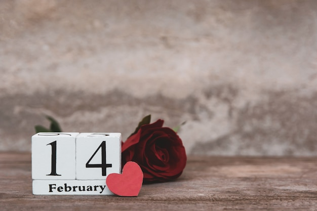 Valentines day with february 14th. wooden white block calendar, red rose and red heart on wood table background with copy space