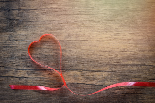 Valentines day with red ribbon heart on wooden background top view copy space