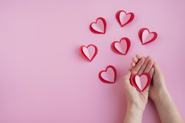 Valentines day. woman's hands hold heart on pink background