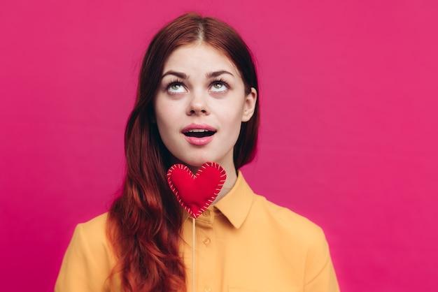 ピンクのクロップドビューでスティックにハートのバレンタインデーの女性