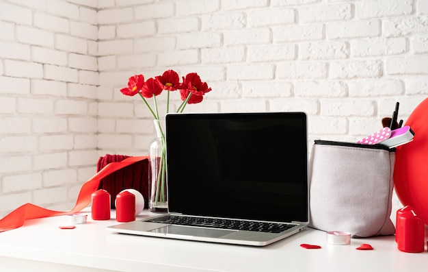 Valentines day and womens day concept. laptop with cosmetic and spa accessories, gift box