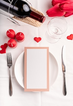 Valentines day and womens day concept. valentines day table setting with menu, plate, bottle of wine top view, mock up design