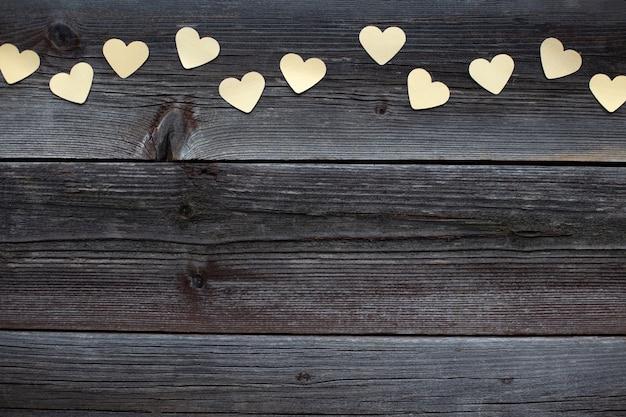 紙の黄金の心と古い素朴な茶色の木製テーブルとバレンタインデーの木製の背景。上面図、コピースペース