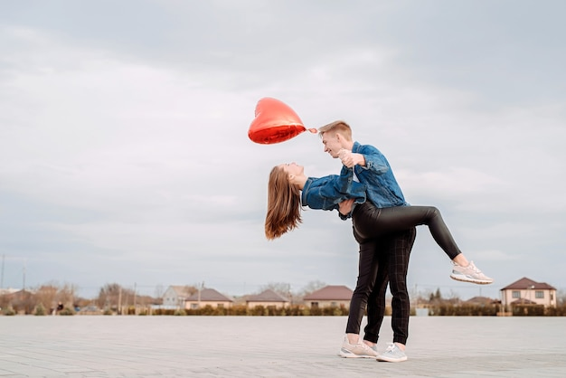 발렌타인 데이. 빨간 풍선을 들고 공원에서 광장에 열정적 인 탱고 춤 젊은 부부
