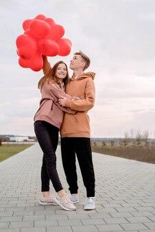 발렌타인 데이. 젊은 부부 포옹과 야외에서 붉은 심장 모양의 풍선을 들고