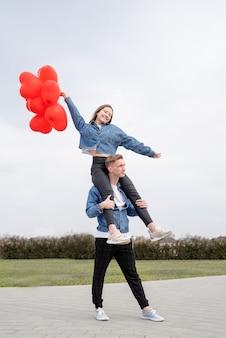 バレンタイン・デー。屋外で赤いハート型の風船を抱き締めて保持している若い愛情のあるカップル