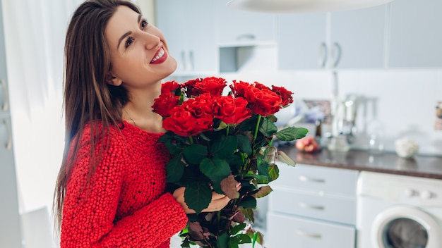 Valentines day. young woman found bouquet of red roses on kitchen. happy girl holding flowers.