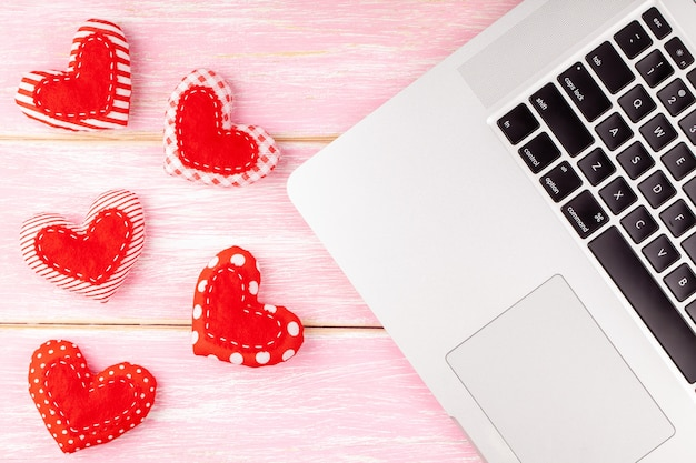 Valentines desktop decoration with red handmade sewed heart gift and laptop