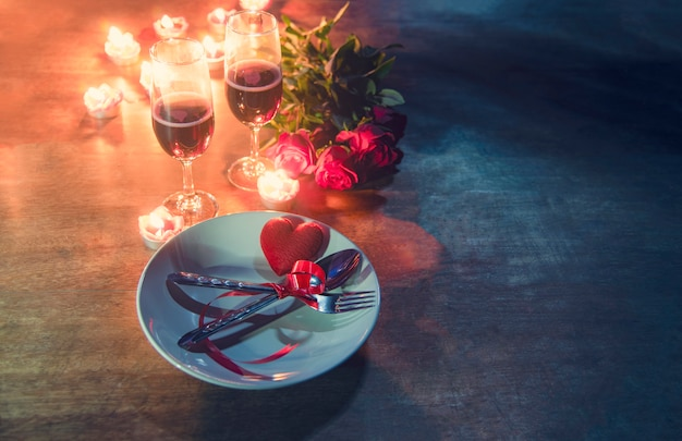 Valentines dinner romantic love concept romantic table setting decorated with red heart fork spoon on plate and couple champagne glass roses