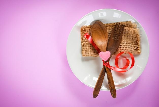 バレンタインディナーロマンチックな愛の食糧および愛の料理のコンセプト木のフォークスプーンと皿の上のピンクの心で飾られたロマンチックなテーブルセッティング