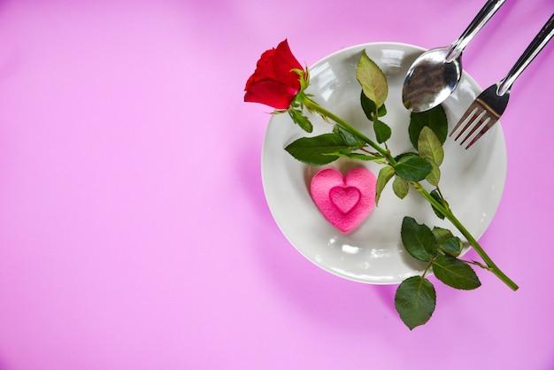 バレンタインディナーロマンチックな愛の食べ物と愛料理フォークスプーンピンクの心とピンクのテクスチャ背景を持つプレート上のバラ