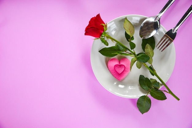 Valentines dinner romantic love food and love cooking fork spoon pink heart and roses on plate with pink texture background