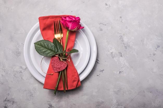 ハートの装飾を設定するテーブルの場所でのバレンタインディナー、バレンタインデーのディナーのためのバラ。上からの眺め。