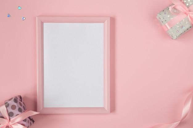 Плоская планировка валентинки с подарками, лентами и блестящими сердцами. день рождения, день матери, день святого валентина фон с копией пространства. вертикальный макет розовой рамки.