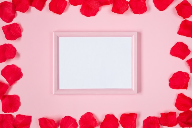 バラの花びら、ピンクのフラットレイとバレンタインフレーム。