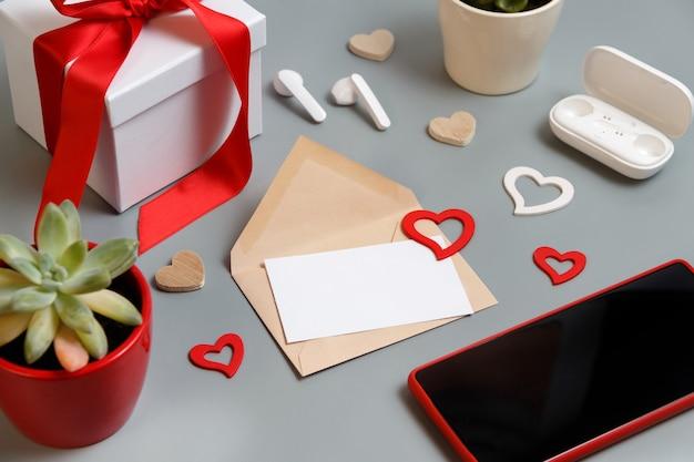 발렌타인 데이 선물 및 하트, 즙이 많은 식물, 이어폰 및 스마트 폰 근처의 블랙 카드가 회색 테이블에 닫습니다.