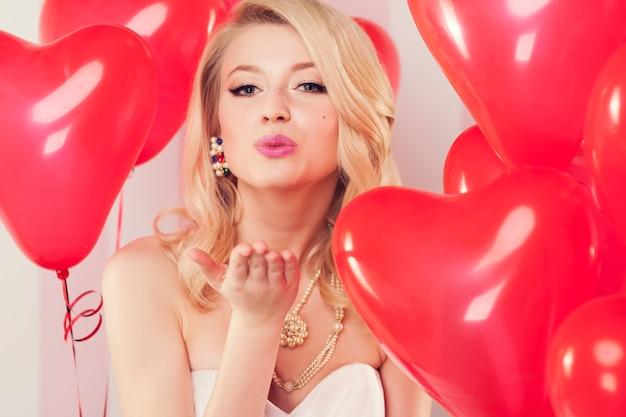 Ragazza di san valentino che soffia baci dolci