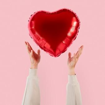 Palloncino a cuore di san valentino tenuto da una persona