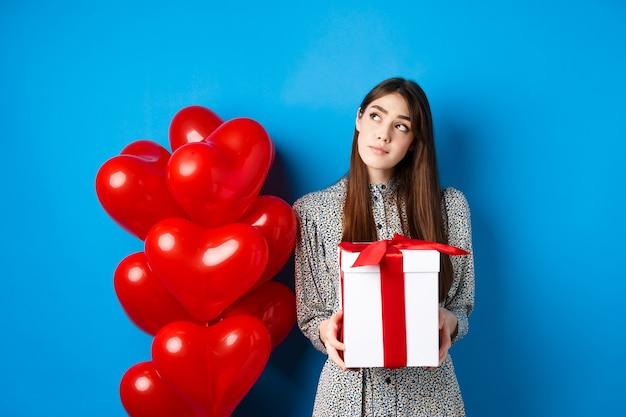 Концепция праздника валентина задумчивая молодая женщина в платье держит подарок и смотрит на верхний левый угол ...