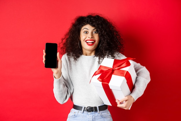 Valentines and lovers day. excited smiling woman with curly dark hair, showing smartphone empty screen and holding surprise gift on holiday, showing online promo, red wall.