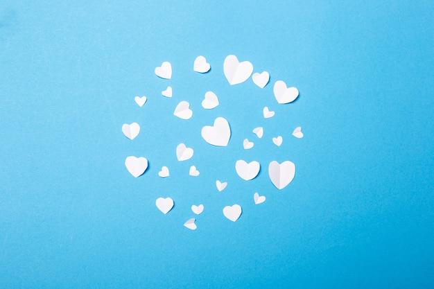 青い背景にハートの形をした紙で作られたバレンタイン。バレンタインデーの構成。バナー。フラットレイ、上面図。