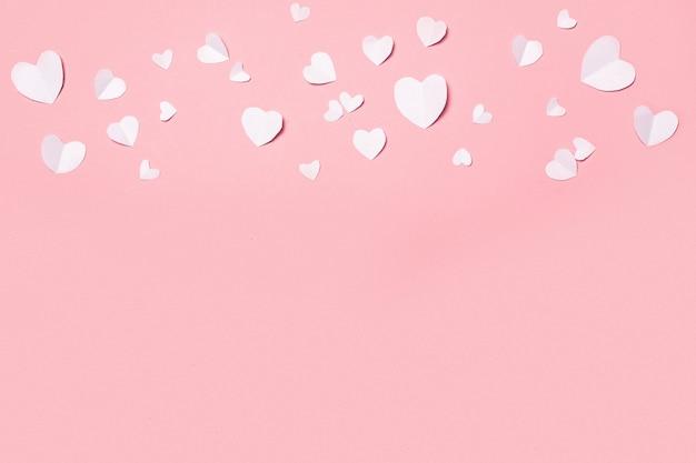 ピンクの背景にハートの形をした紙で作られたバレンタイン。バレンタインデーの構成。バナー。フラットレイ、上面図。