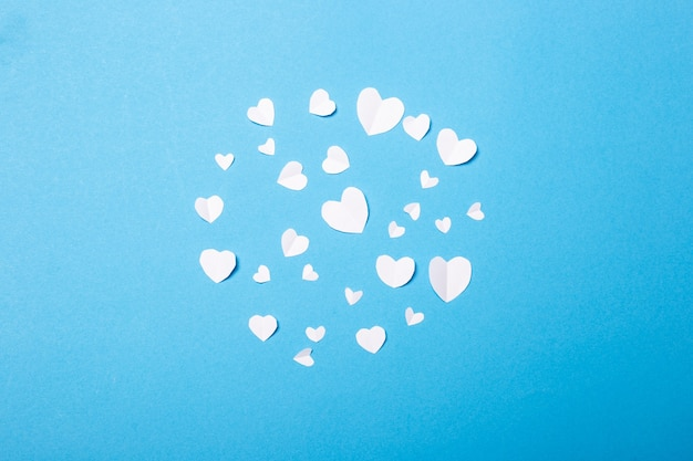 Valentines made of paper in the shape of a heart on a blue background. composition of valentine's day. banner. flat lay, top view.