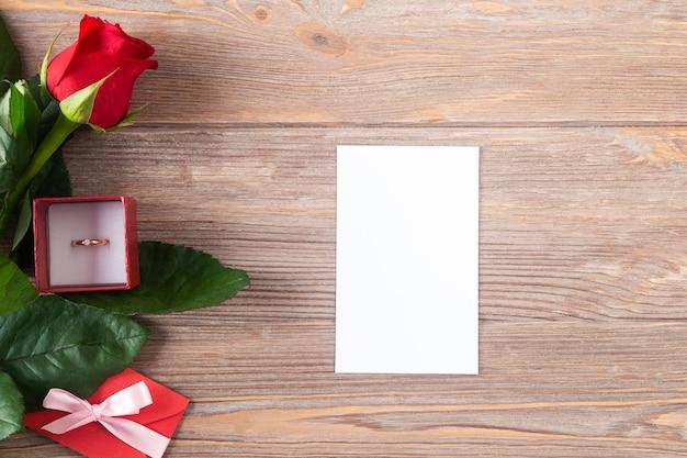 木製の背景に赤いバラと金の指輪、コピースペース、白いカードとフラットレイとバレンタインのモックアップ。