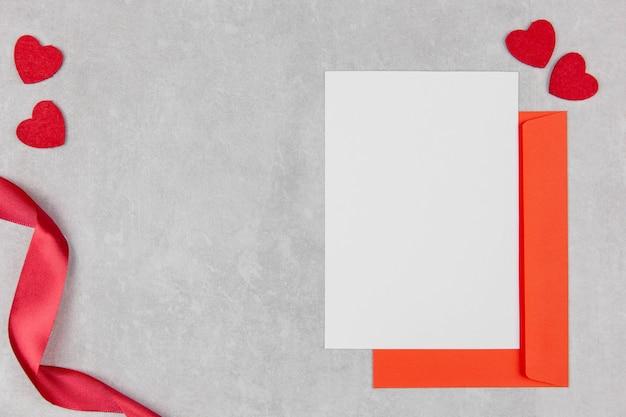 バレンタイン、母の日、または結婚式のフラットは、ハートの紙吹雪が付いている軽いコンクリートの上に空白のグリーティングカードのモックアップと封筒で横たわっていました。