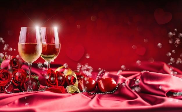 バレンタインや結婚式のコンセプト。ワインカップの赤いバラと2人用のロマンチックな赤の設定。ジュビリーまたは記念日のためのグリーティングカード。