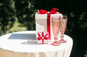 Valentines or wedding day concept with couple of champagne glasses and gift boxes