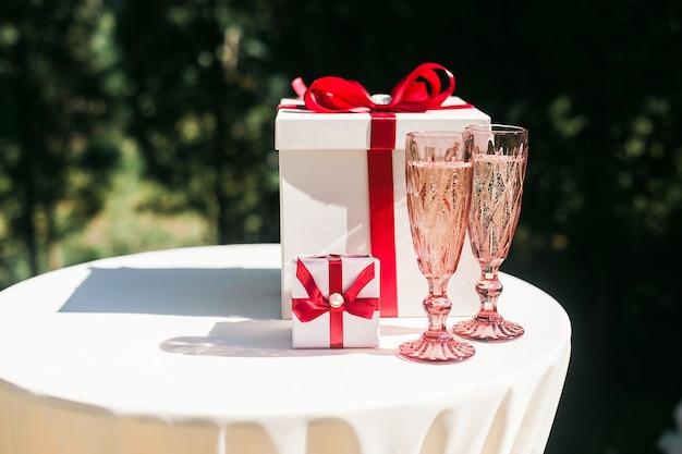 シャンパングラスとギフトボックスのカップルでバレンタインまたは結婚式の日のコンセプト