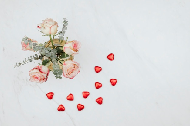 Valentines rose bouquet with red chocolate hearts on a white marble background
