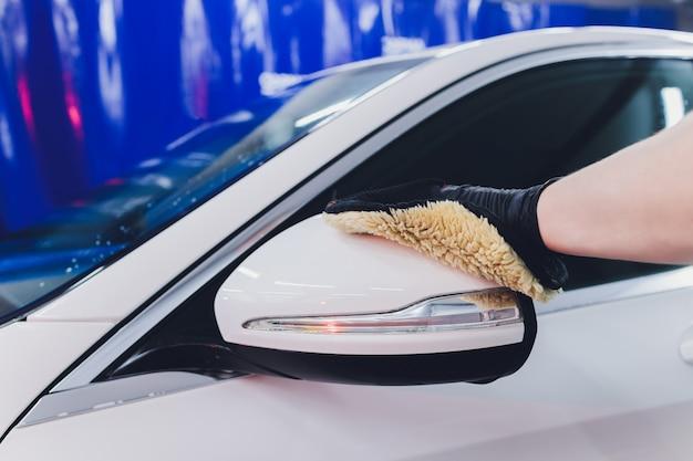 Автомобиль чистки человека с концепцией ткани микрофибры, детали автомобиля или valeting. выборочный фокус.