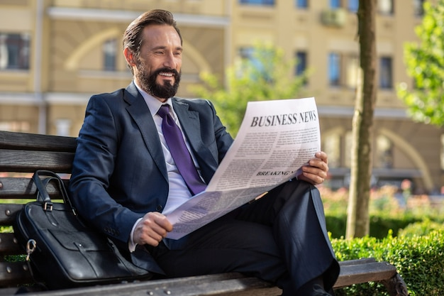 Правильная информация. положительный красивый бизнесмен, читающий газету, сидя на скамейке