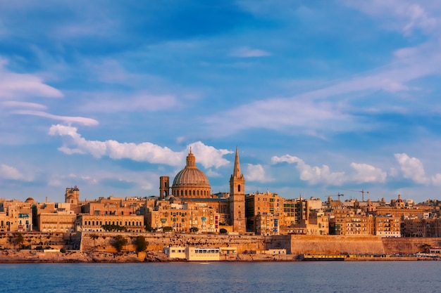 Valletta skyline at beautiful sunset from sliema with churches of our lady of mount carmel and st. paul's anglican pro-cathedral, valletta, capital city of malta