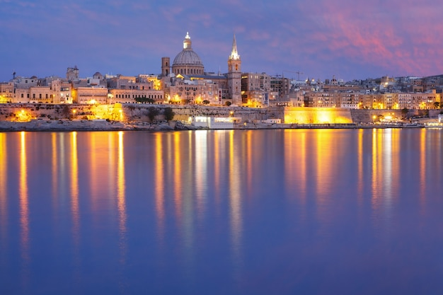 Valletta skyline from sliema with church of our lady of mount carmel and st. paul's anglican pro-cathedral during evening blue hour, valletta, capital city of malta
