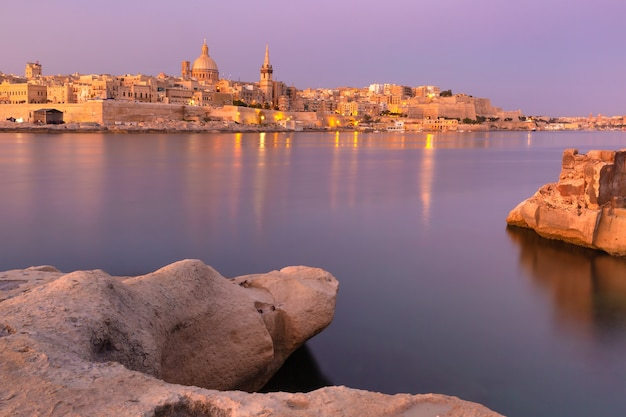 Valletta skyline with churches of our lady of mount carmel and st. paul's anglican pro-cathedral at pink sunset as seen from sliema, valletta, capital city of malta