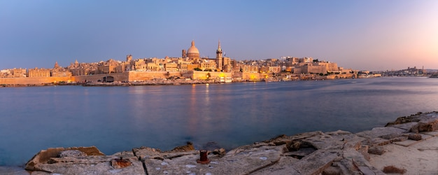 Valletta skyline with churches of our lady of mount carmel and st. paul's anglican pro-cathedral at sunset as seen from sliema, valletta, capital city of malta