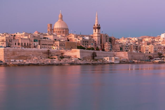 Valletta with our lady of mount carmel church and st. paul's anglican pro-cathedral at sunrise as seen from sliema, valletta, malta