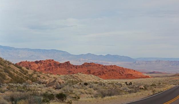 入り口の駐車場からネバダ州の火の谷。灰色と黄褐色の石灰岩に囲まれた真っ赤なアステカの砂岩の露頭