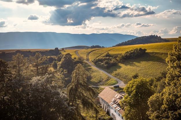 背景に丘があり、底に古い家がある谷
