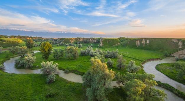 Долина с речным зеленым полем и голубым небом